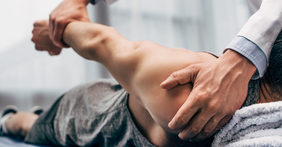 Doctor holding patient's shoulder and wrist